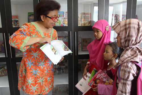 kathy mamahit sedang menunjukan buku-buku baru untuk anak-anak